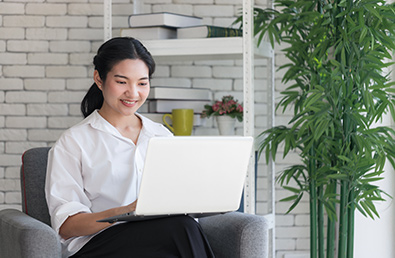 Asian woman sitting in an armchair working on her laptop.