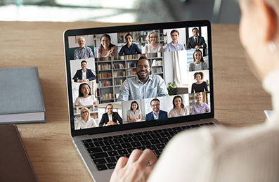 Laptop Screen showing a video call with many people.