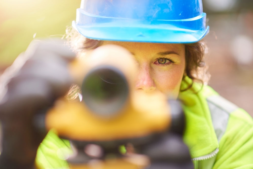 A white woman in blue hard hat measuring with professional tool