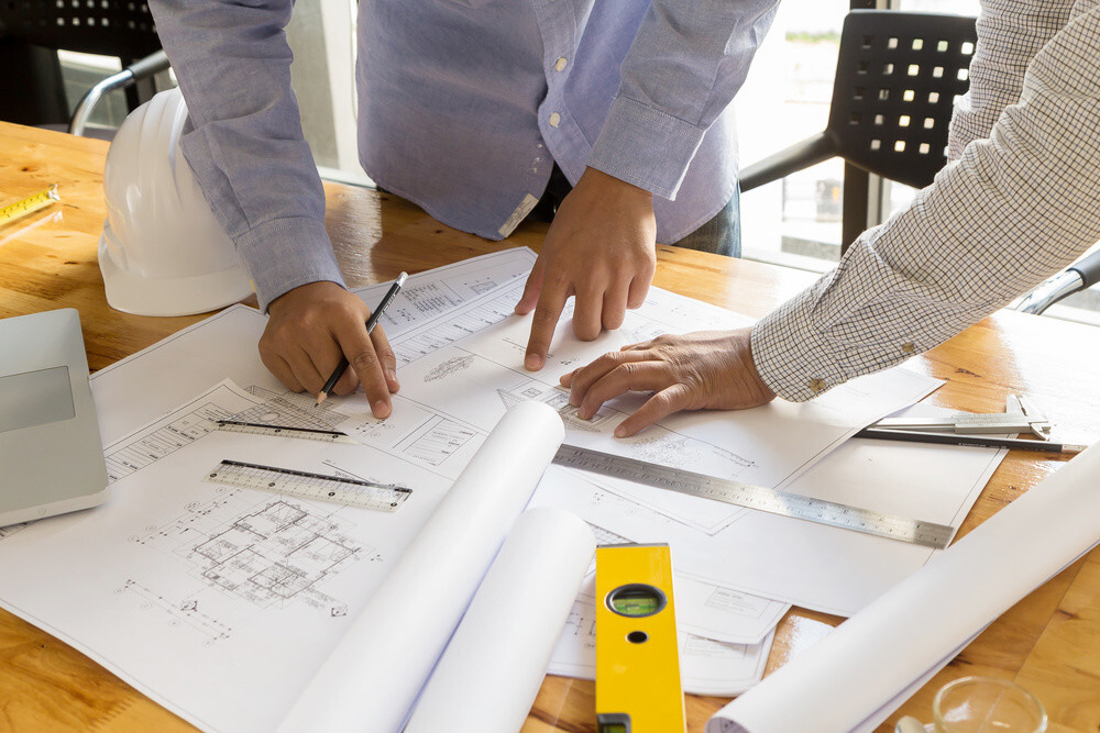 Two men in shirts at work pointing and talking about architectural plans on table