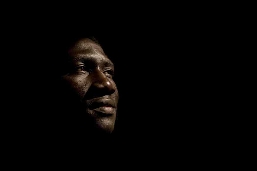 Portrait of Afro-american male in late 20s with his illuminated face the only thing visible against black background