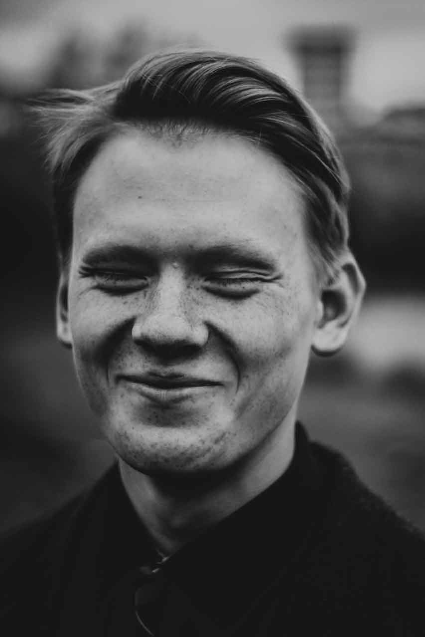 Black and white portrait of young male smiling and eyes closed