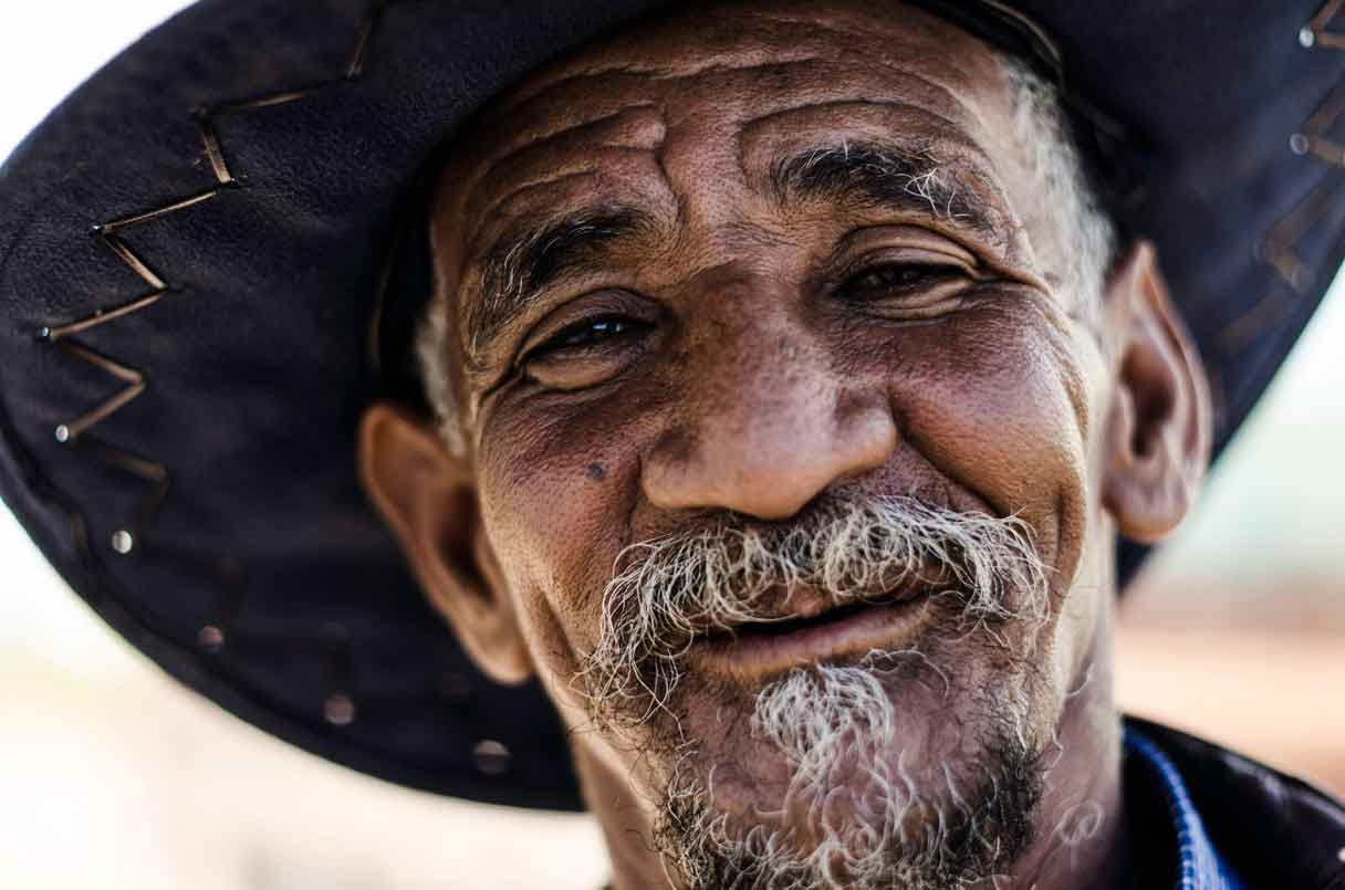 Poertrait of a smiling male in his 70s with moustache and wide brimmed hat