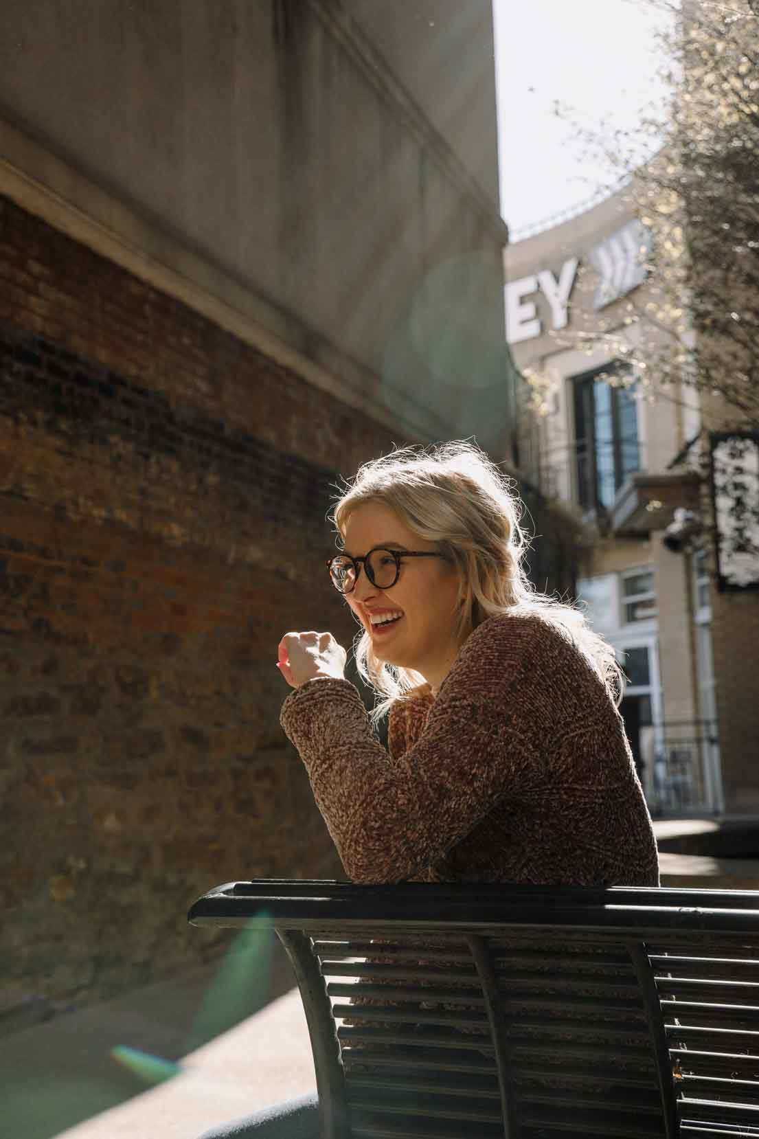 Photo of female in late twenties wearing glasses with blond hair sitting on a bench smiling