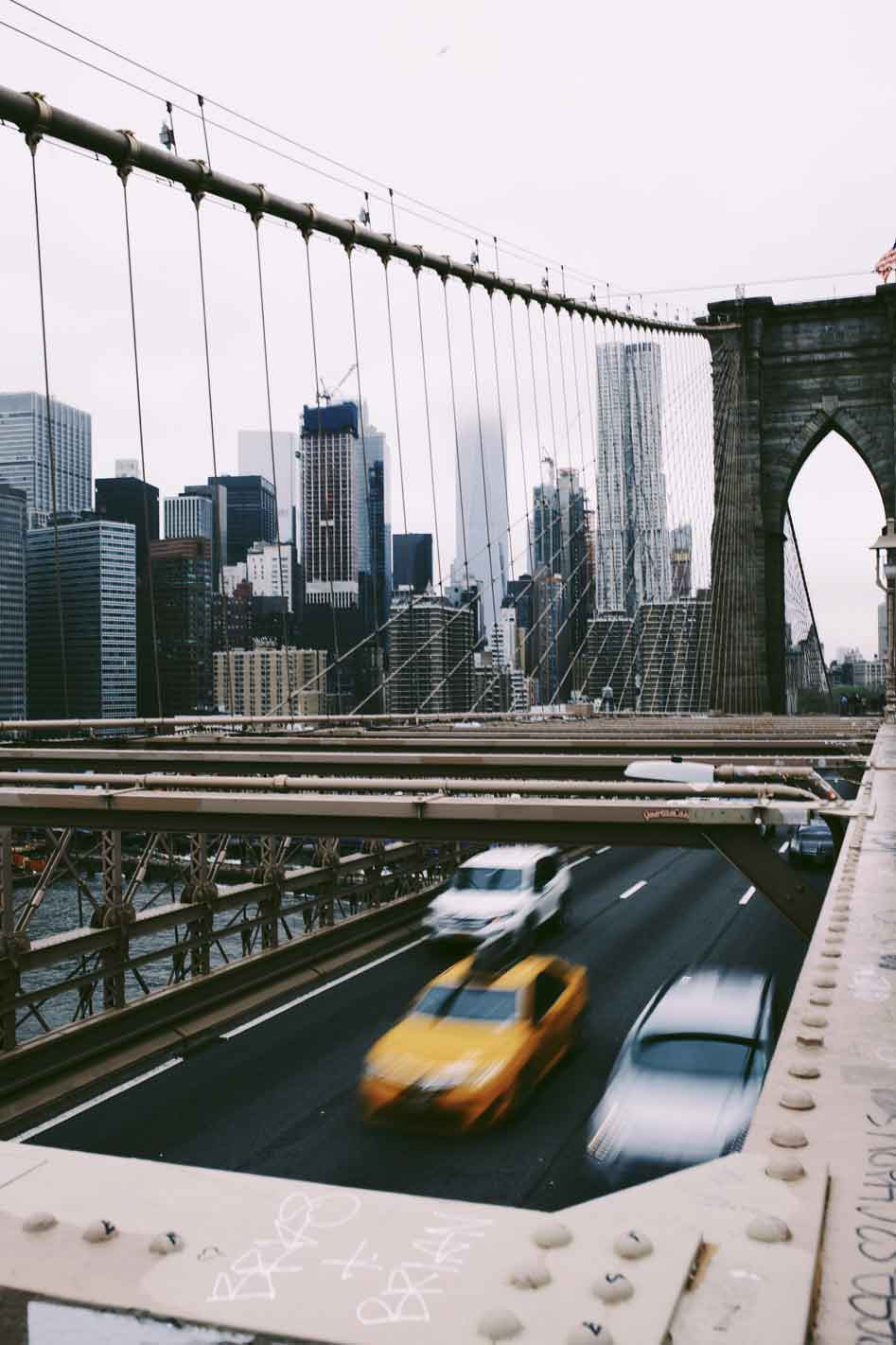 Brooklyn Bridge with moving cars and Manhattan skyscrapers in the background