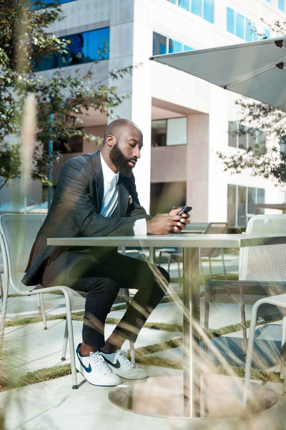 Male in 30s with beard looking at phone outdoors sitting on metal chair at metal table wearing a suit, white trainers and no socks