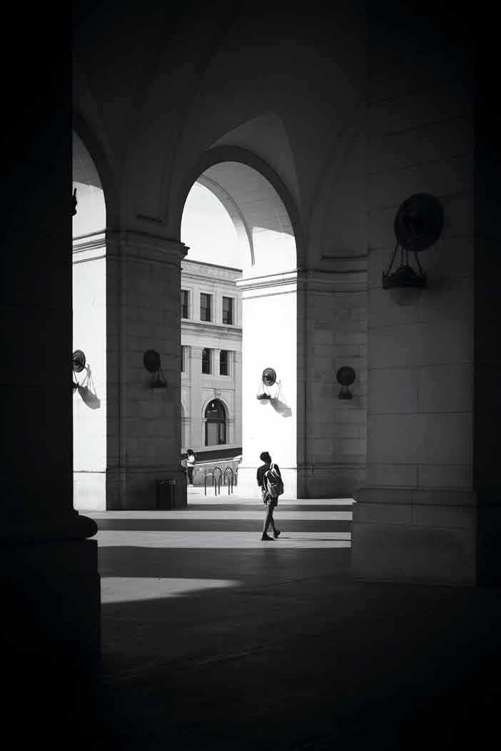 black and white photo of a person walking between looming university buildings
