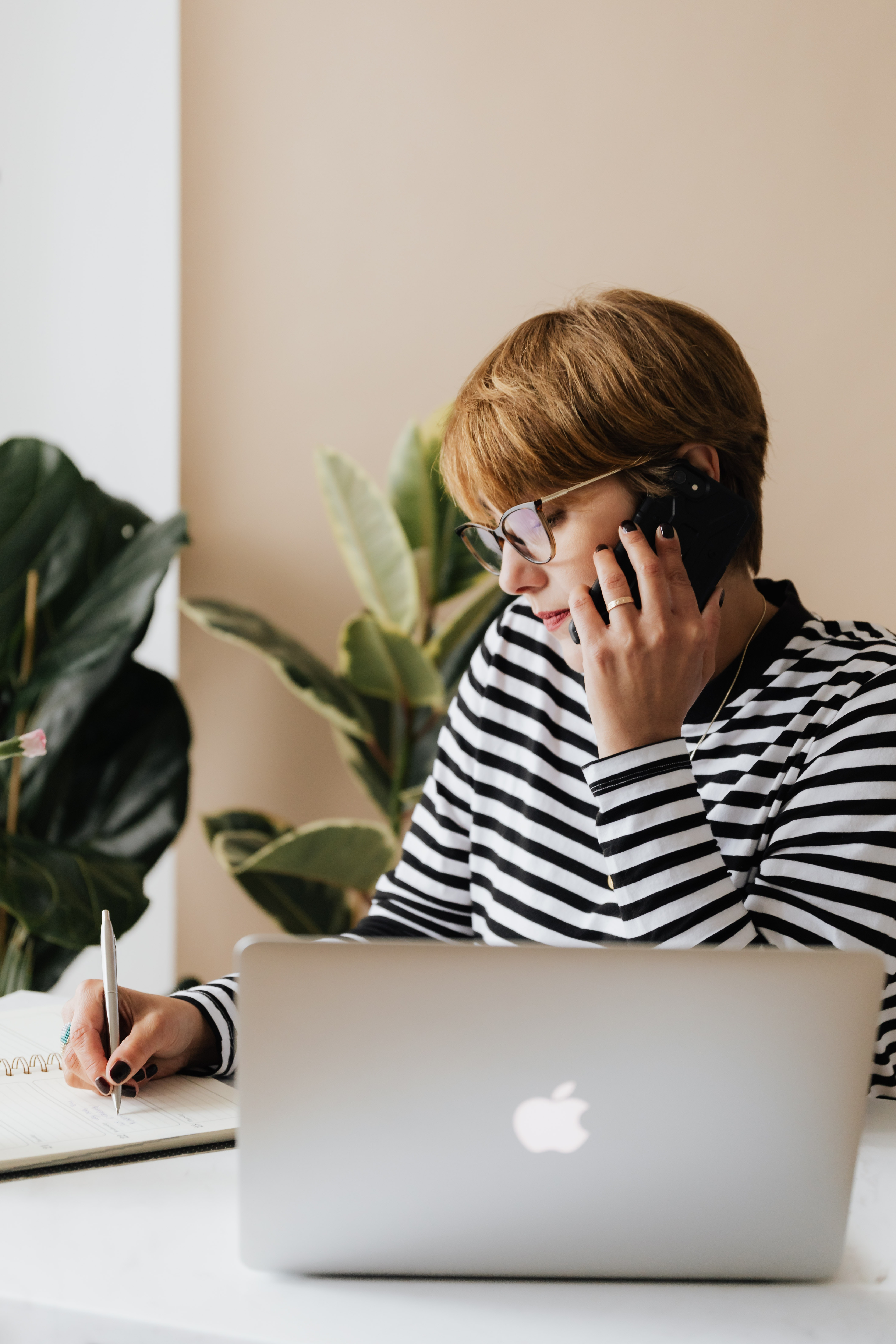 Entrepreneuse au téléphone écrivant dans un cahier