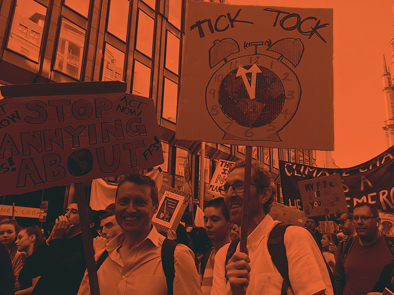 Alan stands among a climate emergency protest, holding a signs which says 'Tick Tock'