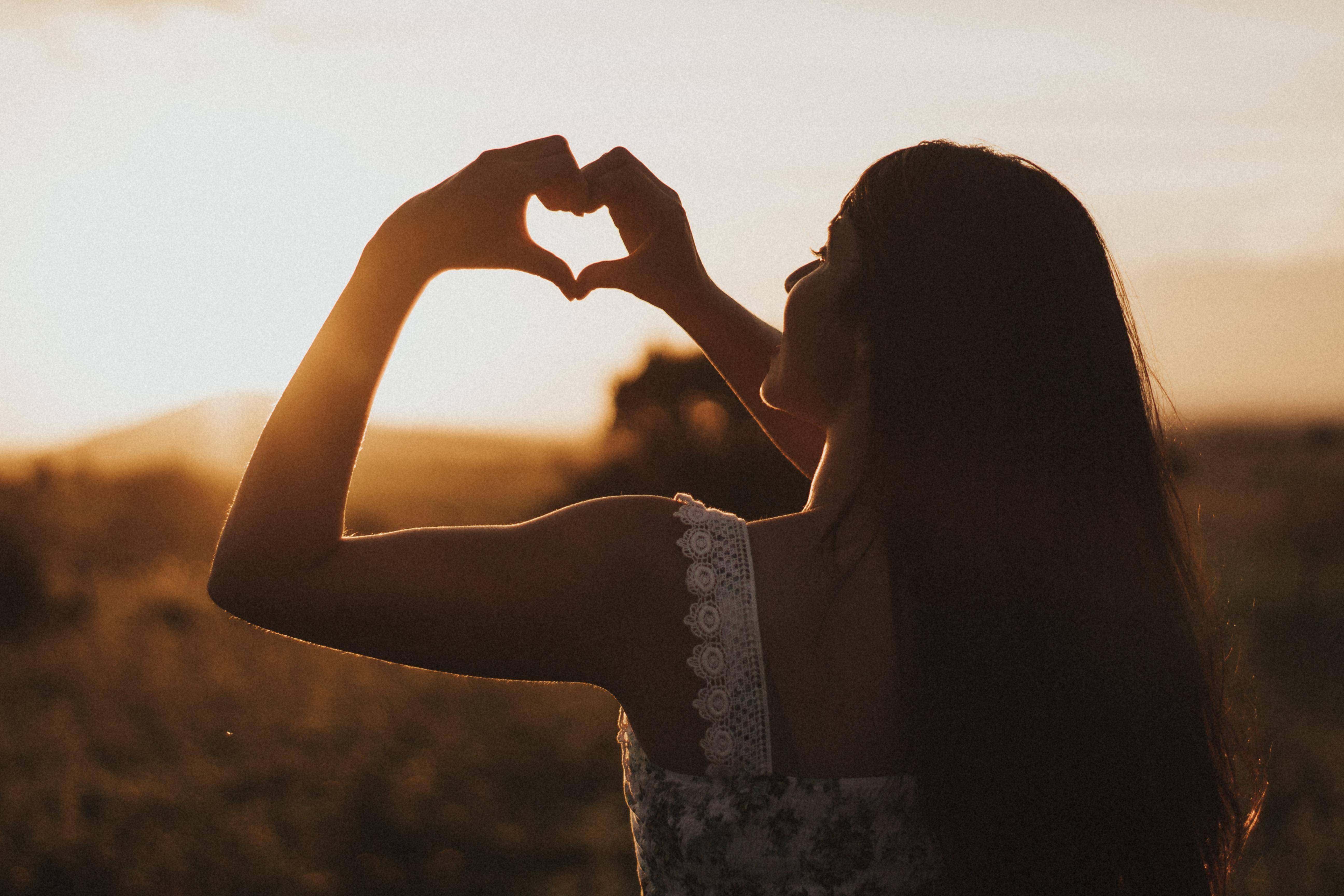 Foto einer langhaarigen Person, die von hinten zu sehen ist. Mit ihren Händen formt sie ein Herz.