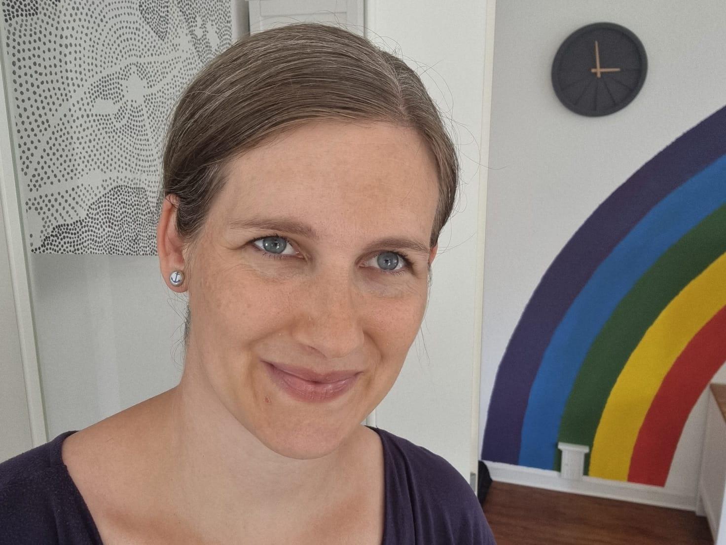 Porträt von Elternberaterin Elena Schwarzer. Sie lächelt, neben ihr ist ein auf die Wand gemalter Regenbogen zu sehen.