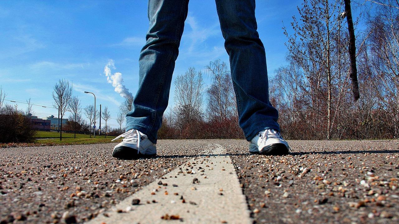 Ein Mensch, der breitbeinig über einem Seitenstreifen auf einer Fahrbahn steht.