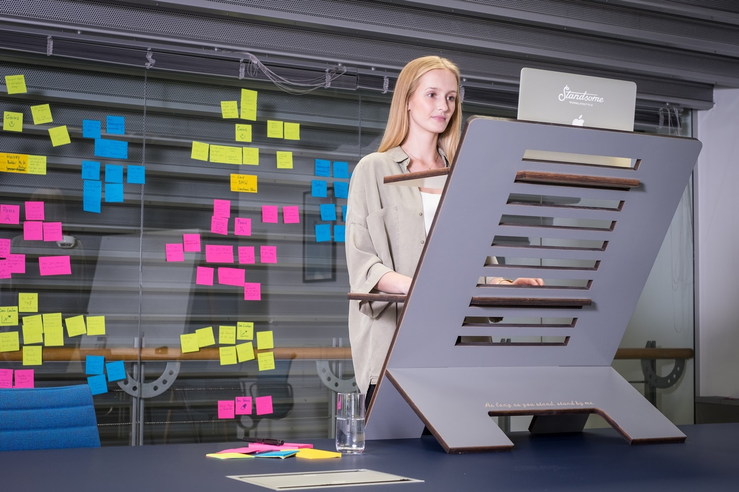 Woman working on a large standing desk with many post-its behind