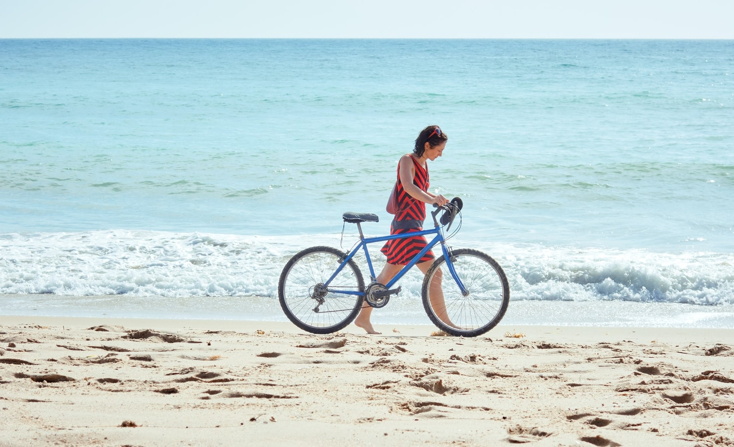 Woman walking with a bicycle on the beach
