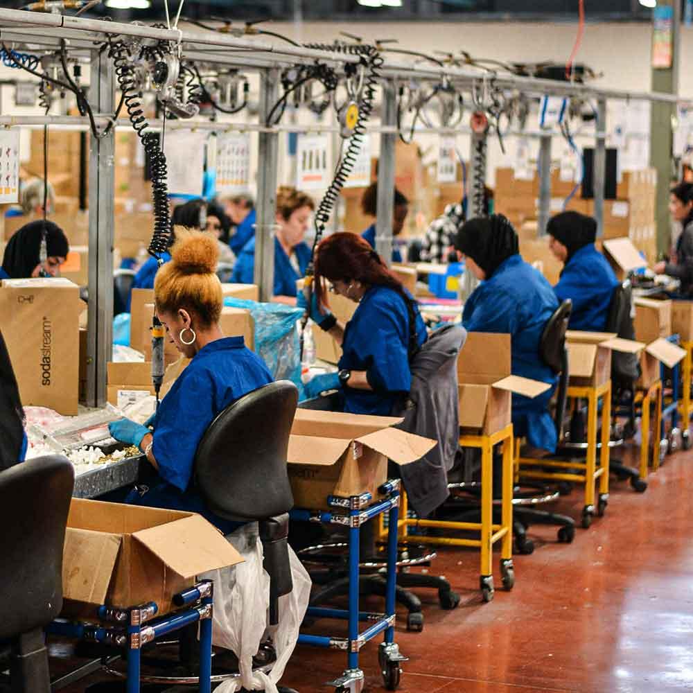 Línea de producción conformada por mujeres en una fabrica manufacturera