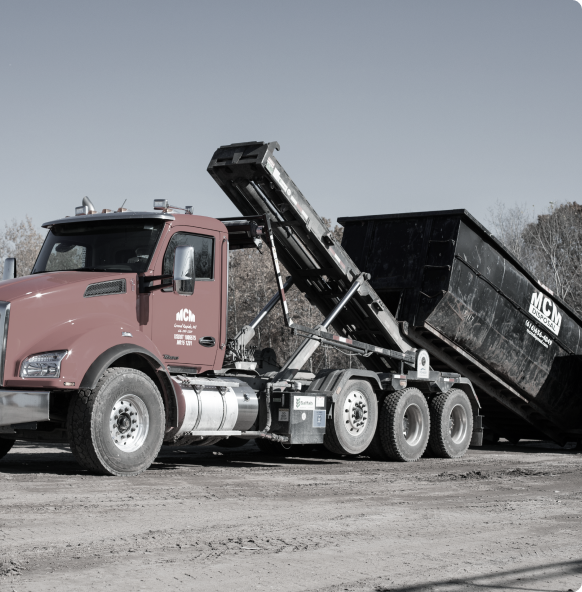 A dump truck drops a roll off container