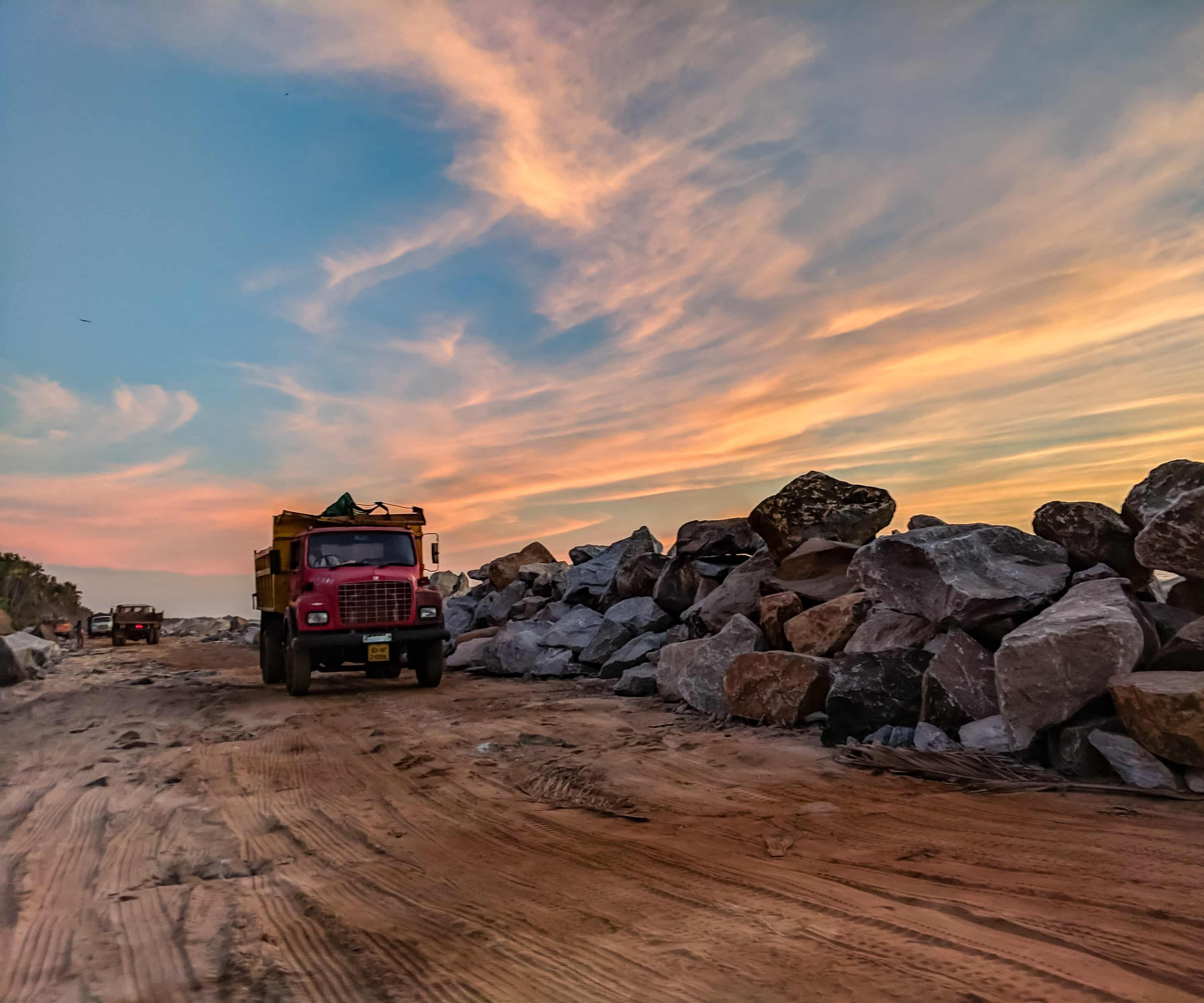 A hauling truck rounds the corner during sunset