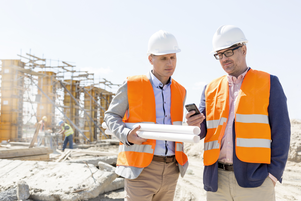 Two men look at their cell phone on a construction site