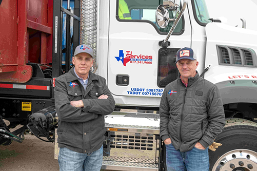 TJ Services owners stand beside their hauling truck