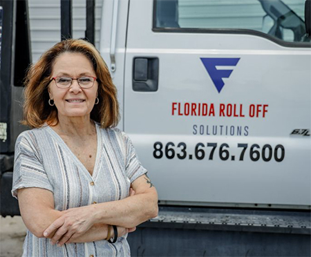 Pam Mosser stands next to her Florida Roll Off Solutions hauling truck