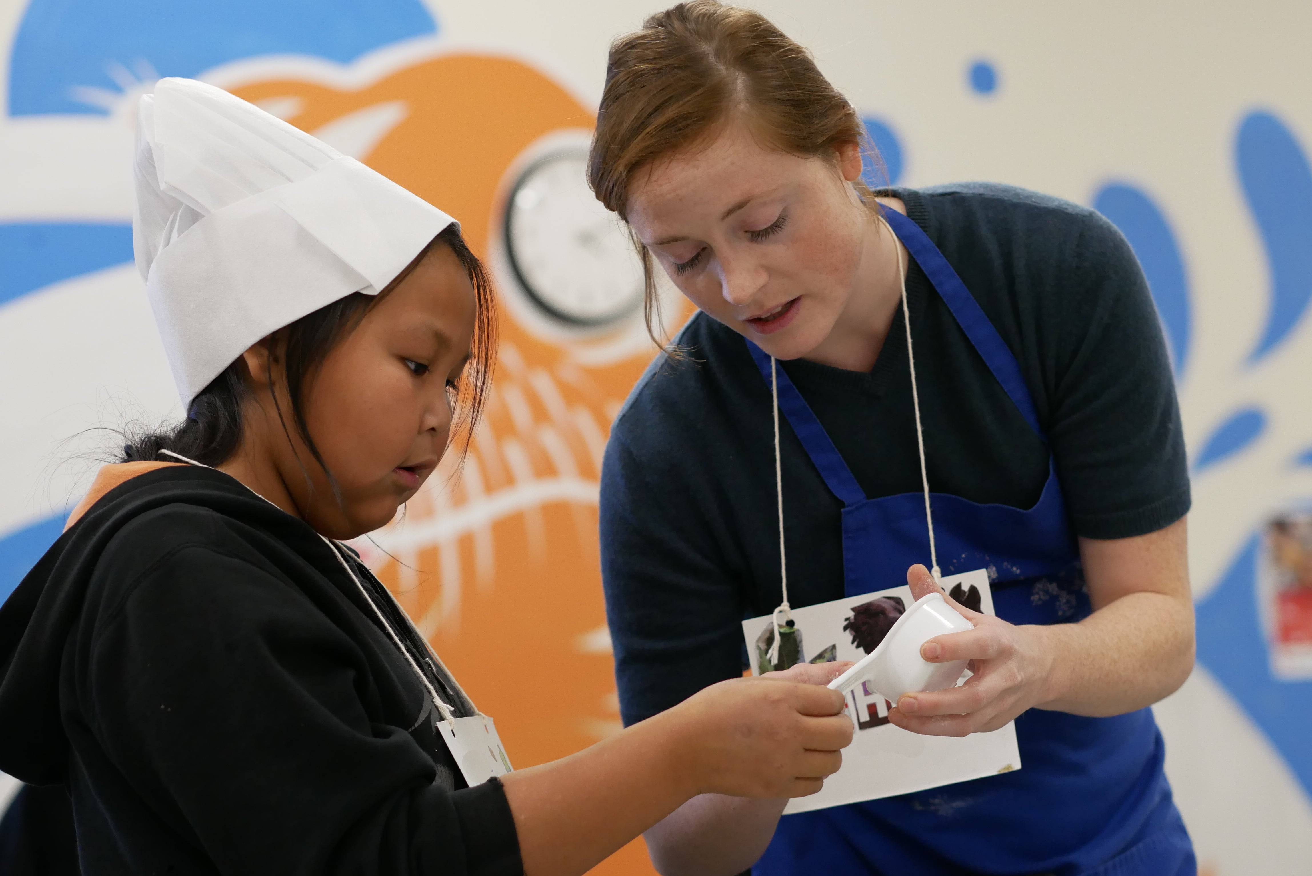 An adult helping a child use a measuring cup as part of Kids' Cooking Club