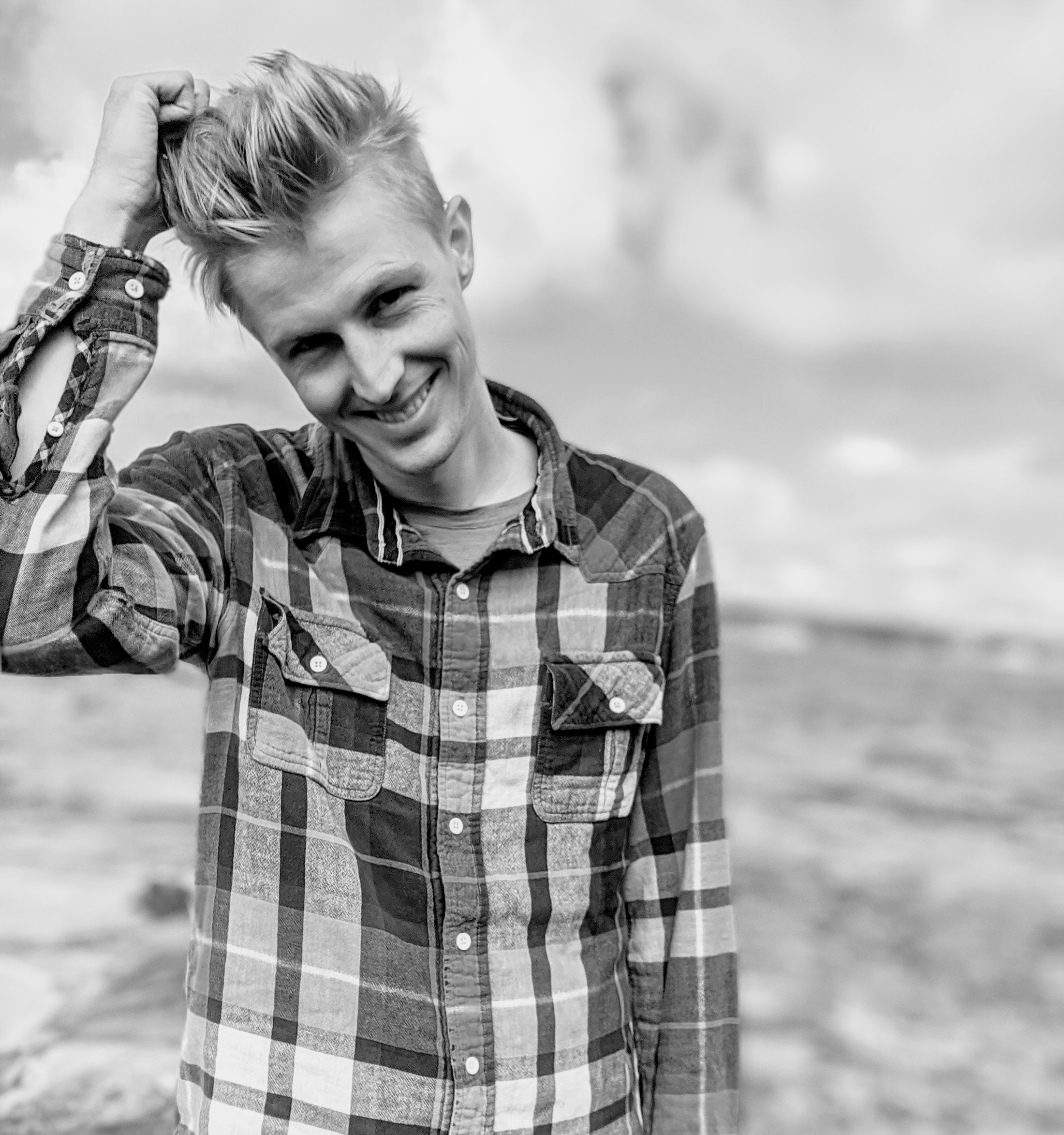 A man with medium blonde hair stands in front of Lake Superior. The image is black and white and he is holding his hair on top of his head with his right hand. He's wearing a buttoned up plaid shirt.