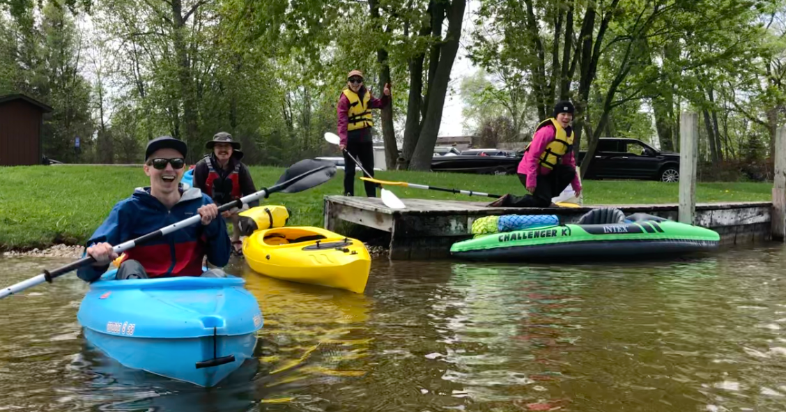 David is kayaking towards the person taking the photo, and three people are on shore getting into their kayaks. Everyone is holding paddles and wearing life jackets as they step off the grass and the wooden dock into their kayaks.