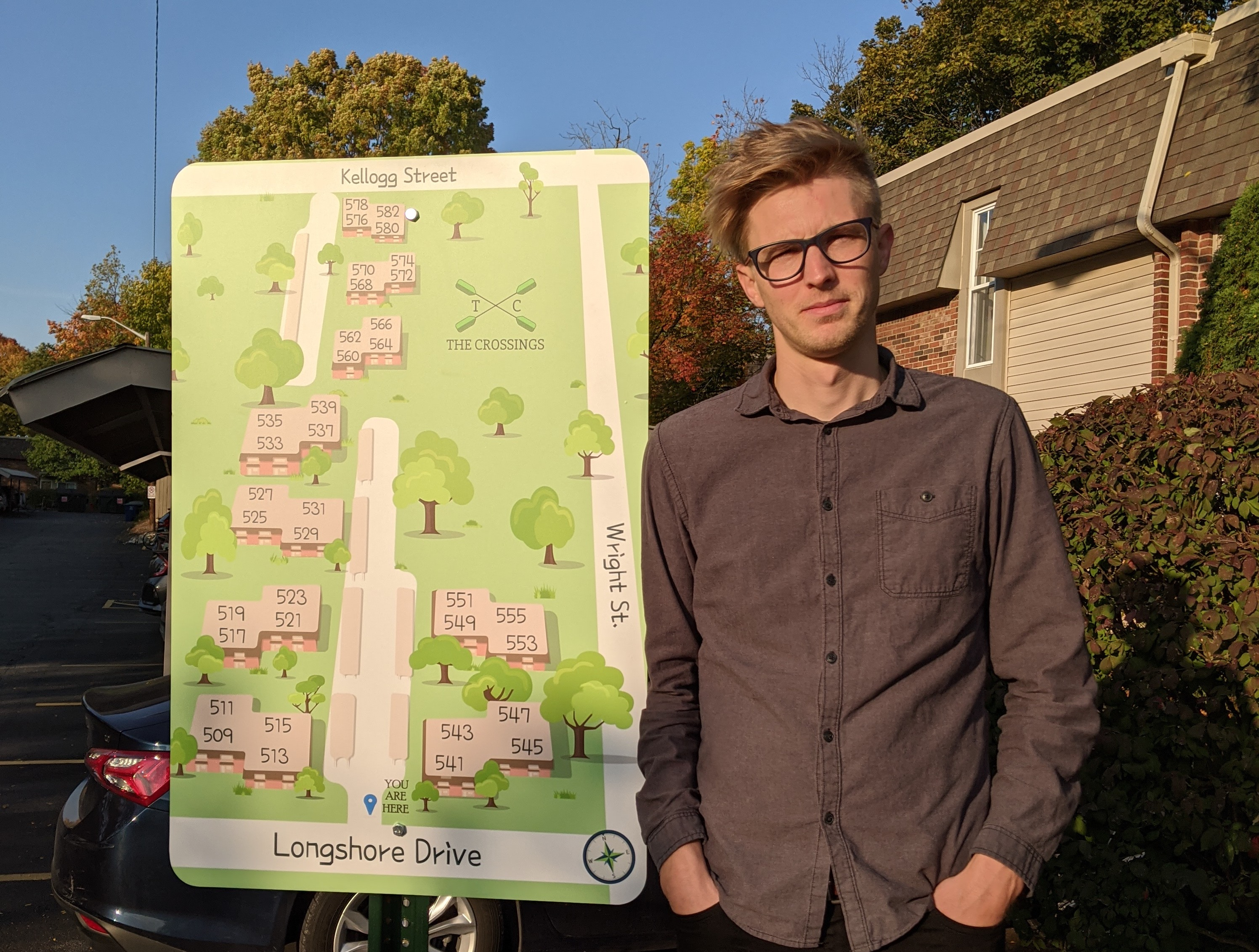 David stands next to a green sign with a map of the buildings in his apartment complex. You can see a building and a bush behind him to the right. His hands are in his pocket and he looks amused that they put up a sign without telling him they were going to ahead of time.