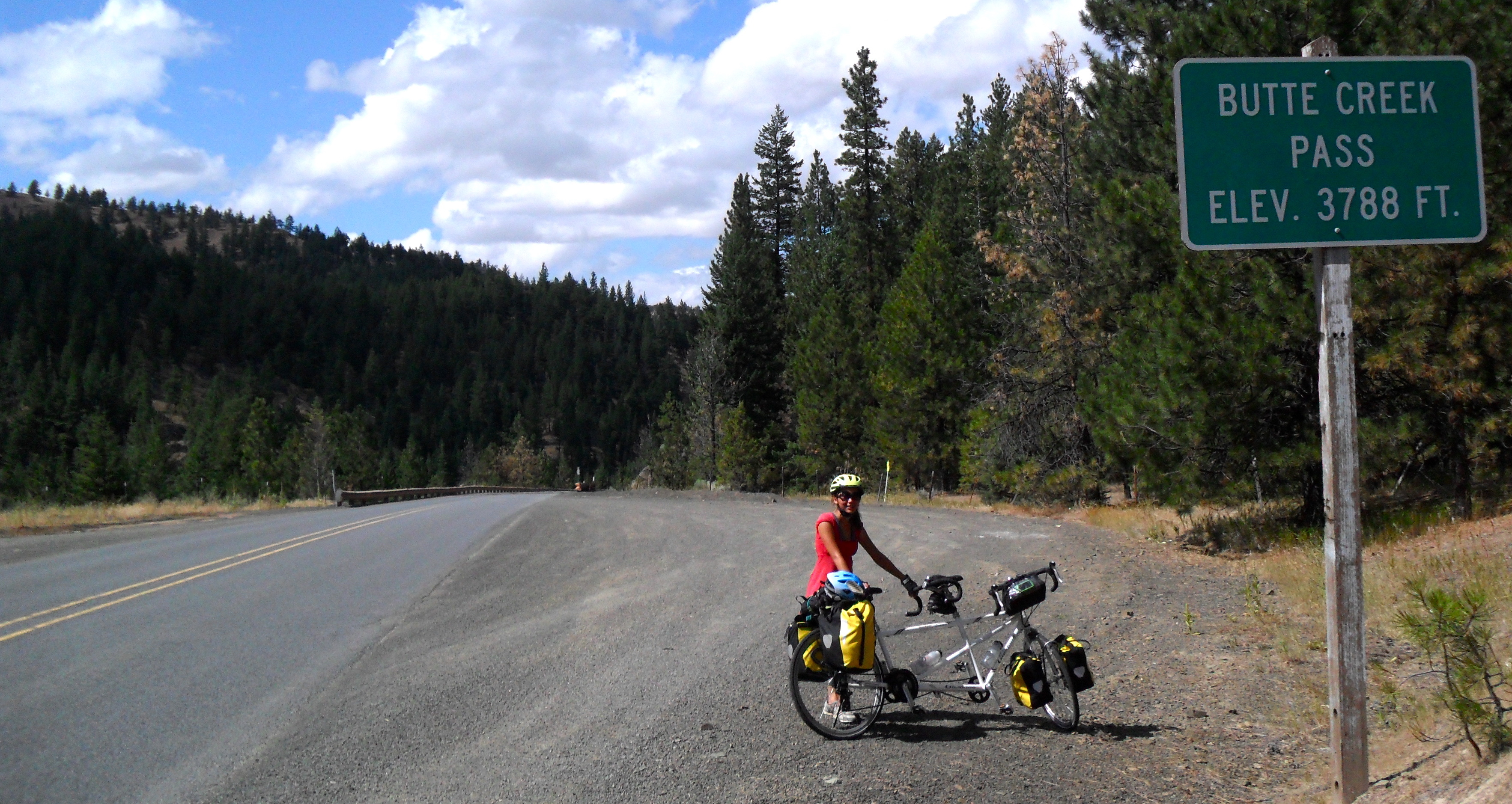 """A woman in a red dress stands on the right side of an empty road behind a white tandem bicycle with panniers on the front and back. A green sign is in the foreground and reads """"butte creek pass, elevation 3788 feet"""". Some green conifers are in the background and blue sky with some clouds."""