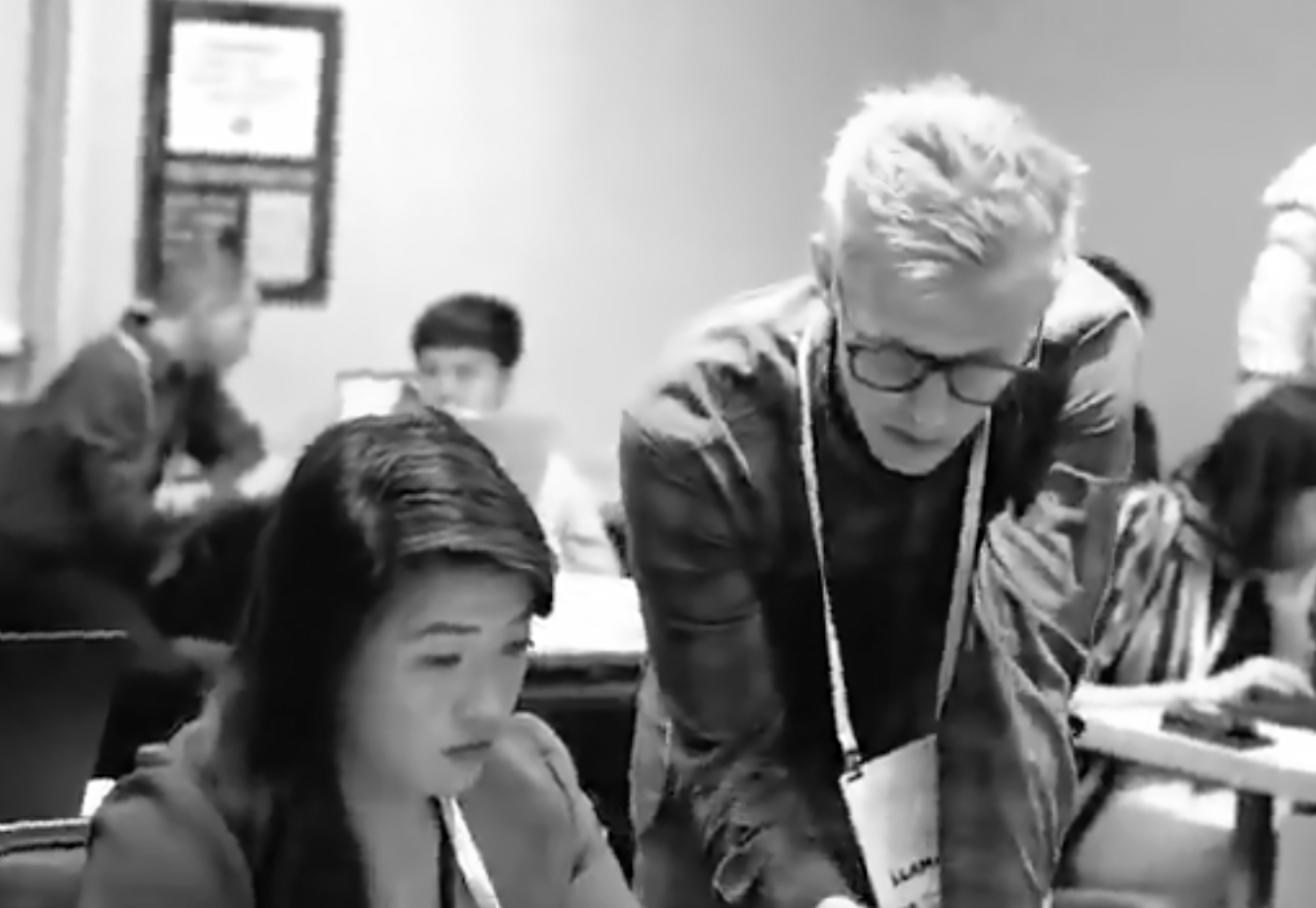 David leans over a woman with dark hair. He has glasses on and a white lanyard. He's in a room with several people in the background looking at their laptops.