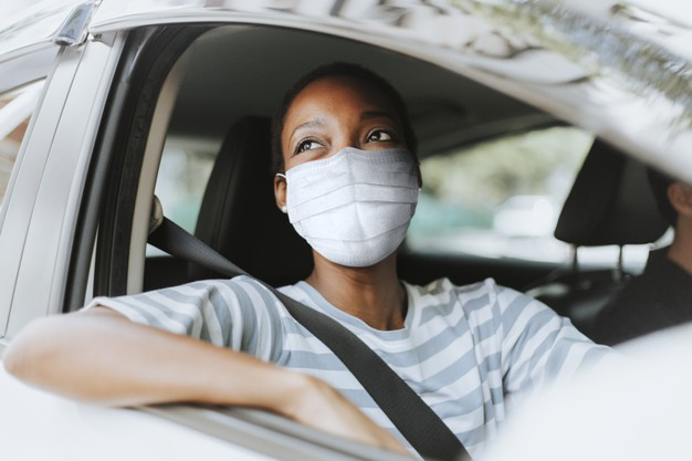 Woman in car with covid mask