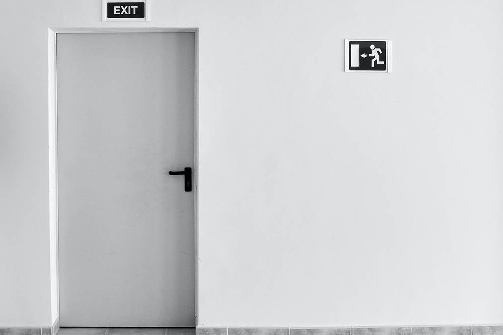 Door with an exit sign to represent breaking a commercial lease
