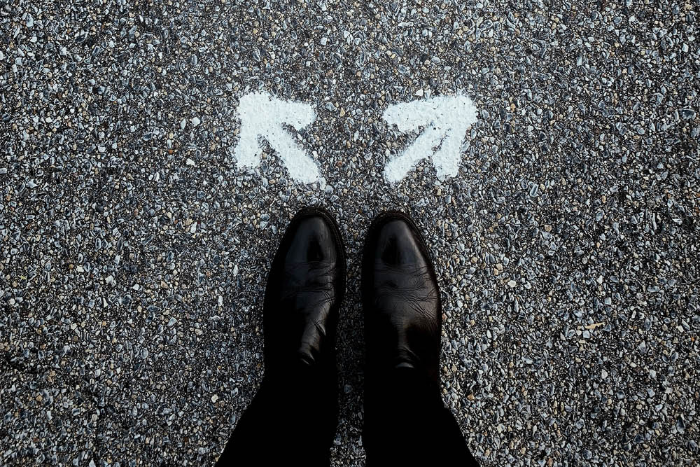 man standing at two arrows on road representing choosing whether to relocate or to stay in current premises