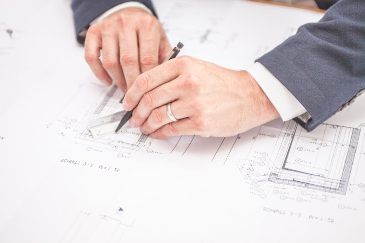 Image of a person working on building plans | Make Good Clause Article