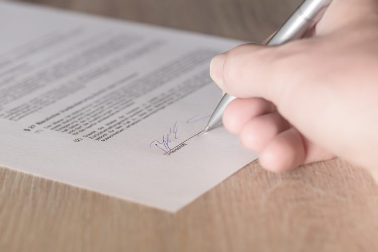 Image of a persons hand signing a sublease | Negotiating sublease article