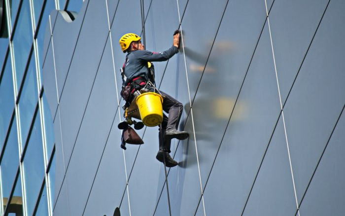 Worker cleaning the side of a commercial building