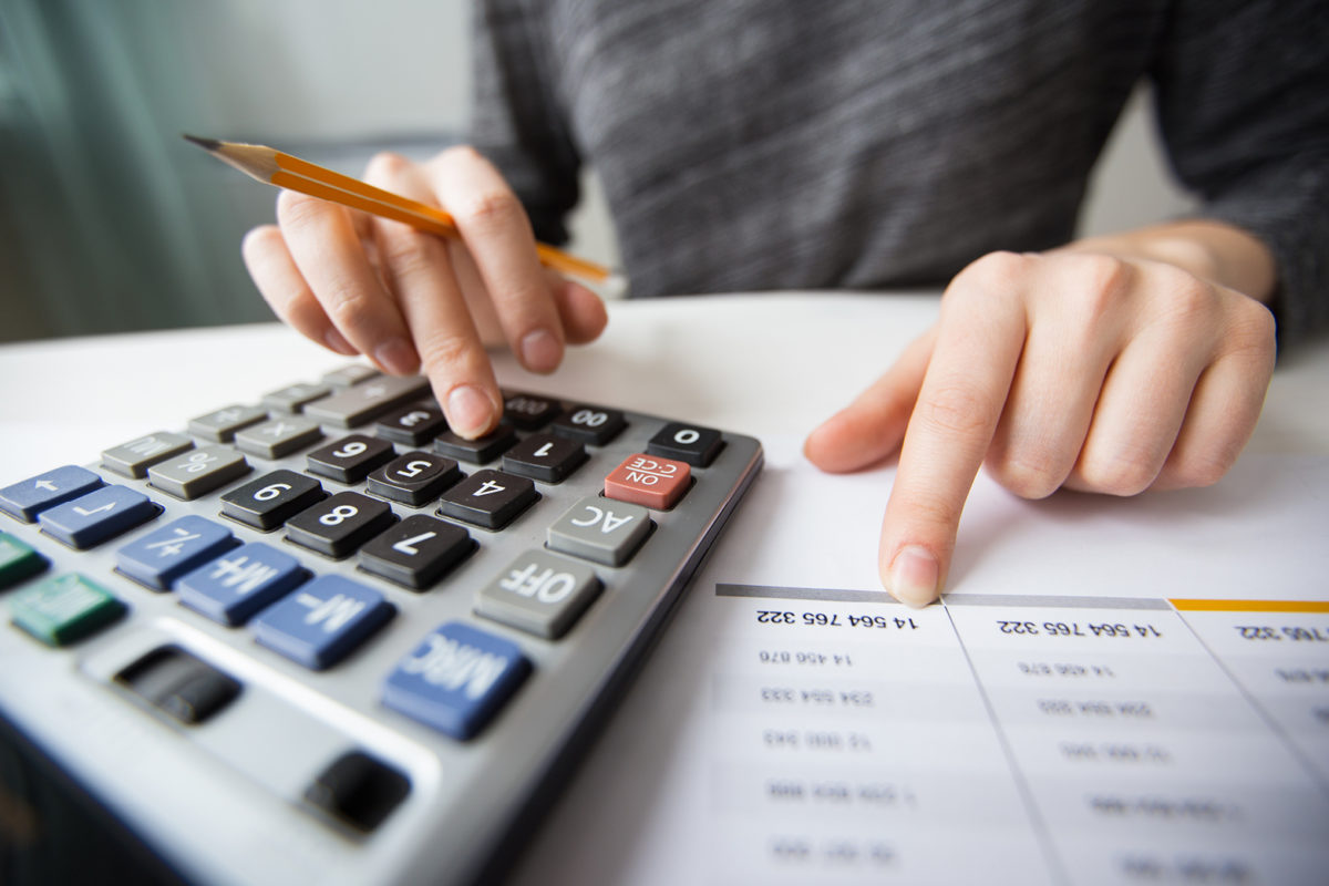 image of man using a calculator representing someone calculating commercial lease outgoings