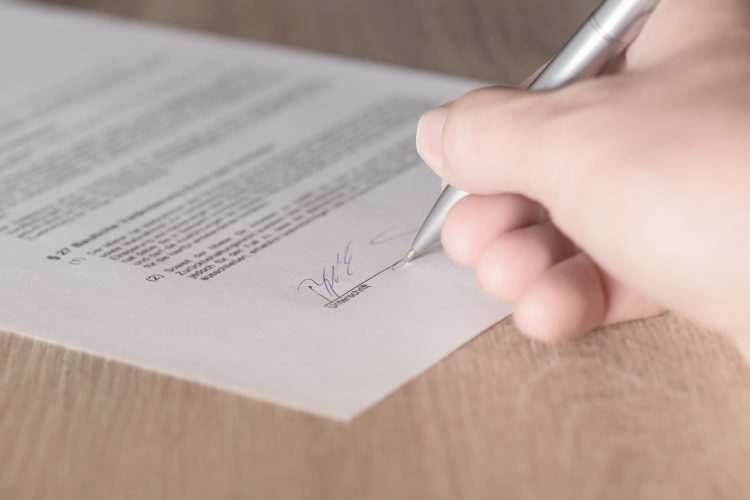 Image of someone signing a commercial lease   Commercial real estate terminology in Singapore article