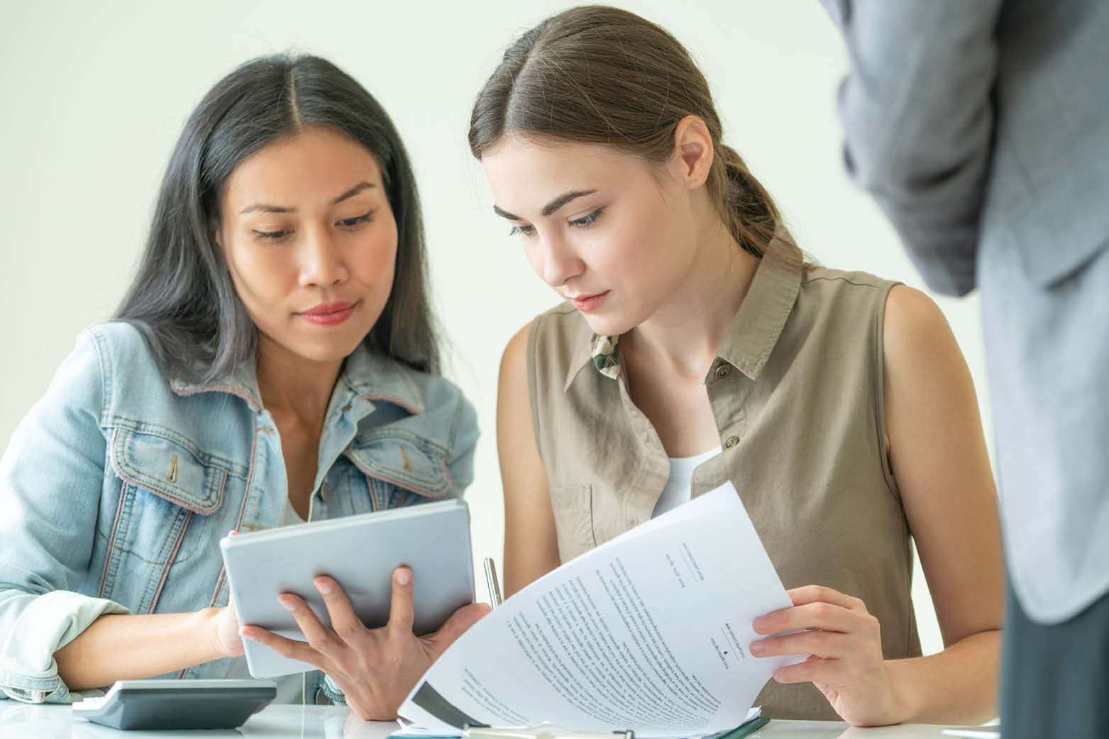 women working through contract full of commercial real estate terms