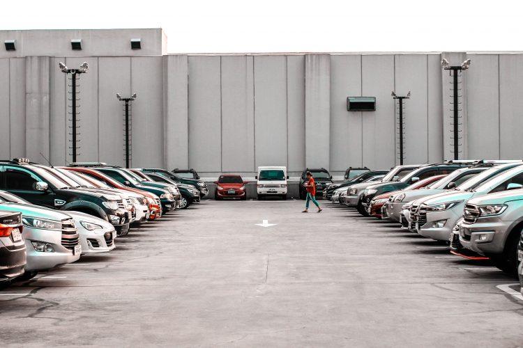 A person walking through a staff car park | Car parking article