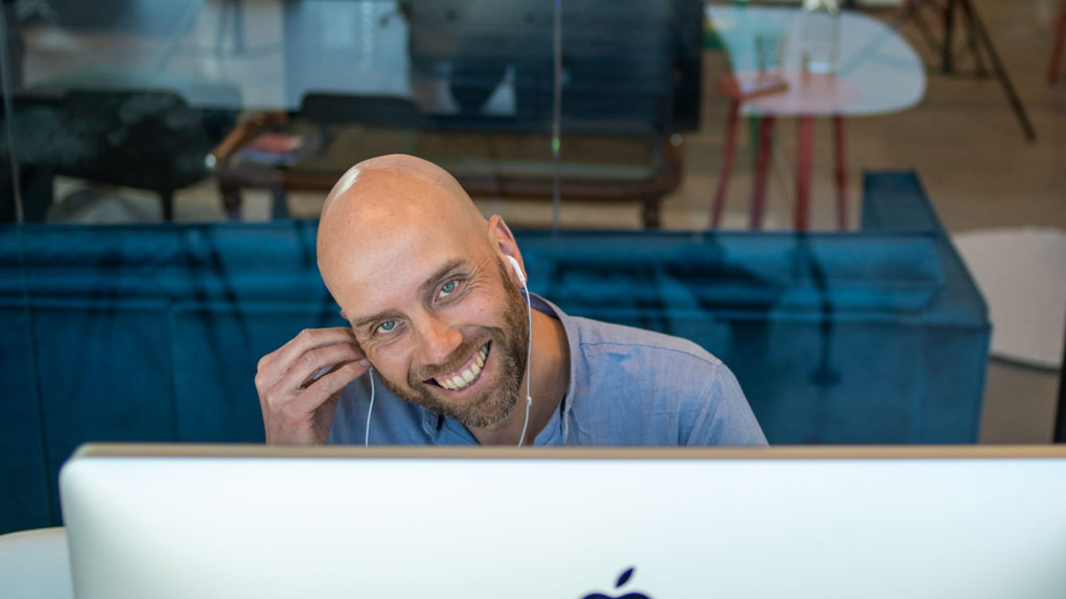 Online Facilitator smiling to camera while sitting behind a large computer screen