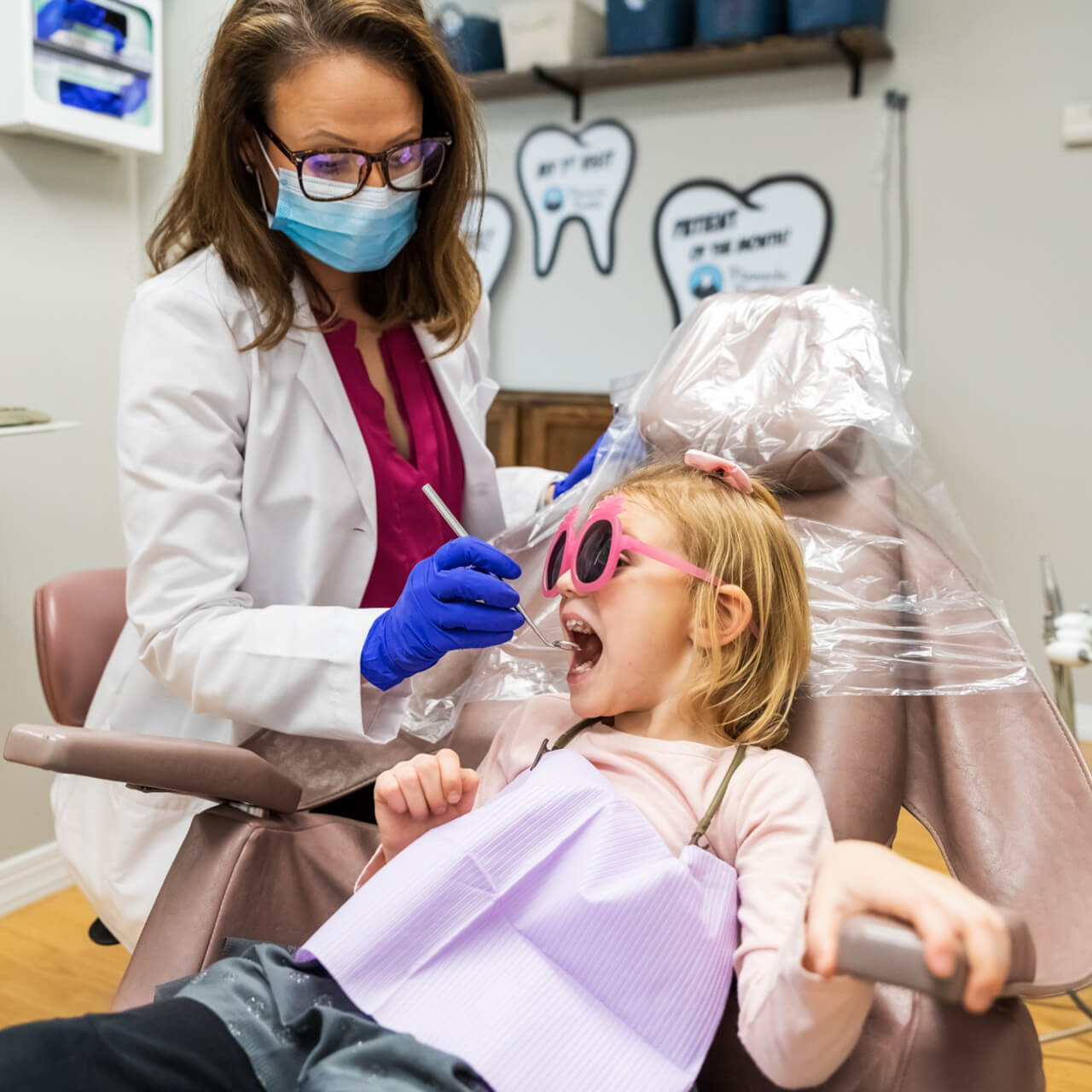 Dr. Megan cleaning a child's teeth during an annual checkup