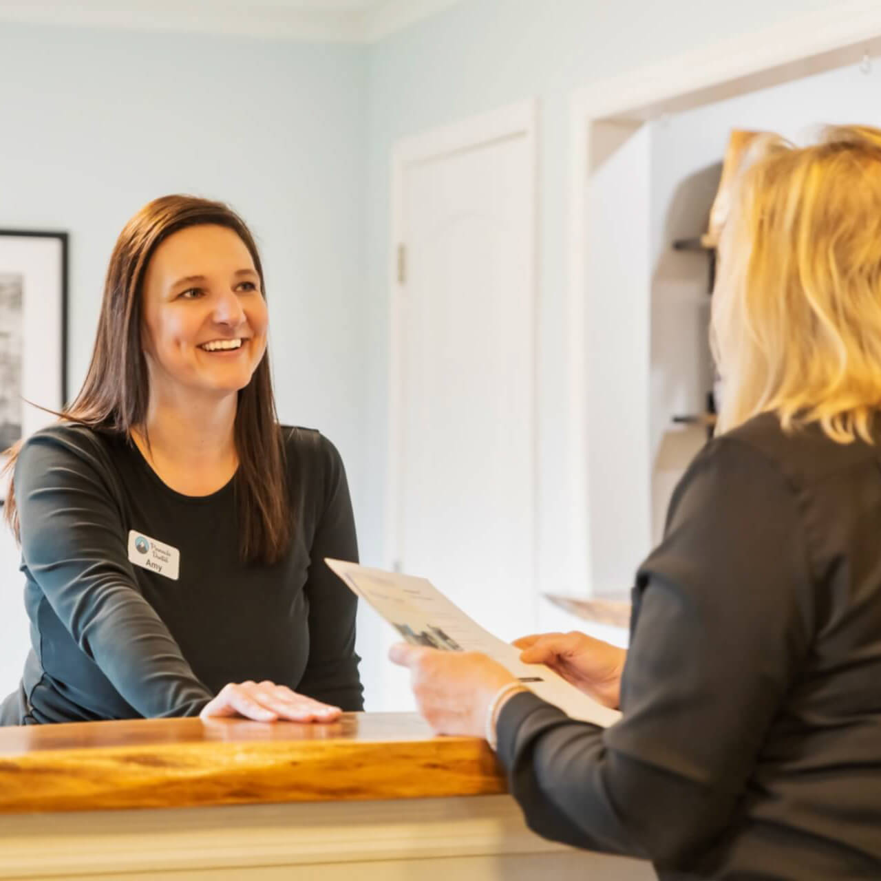 A satisfied patient speaks to reception after treatment with Dr Kottman