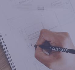 Foto de uma mão desenhando à lápis um esboço de aplicativo mobile.