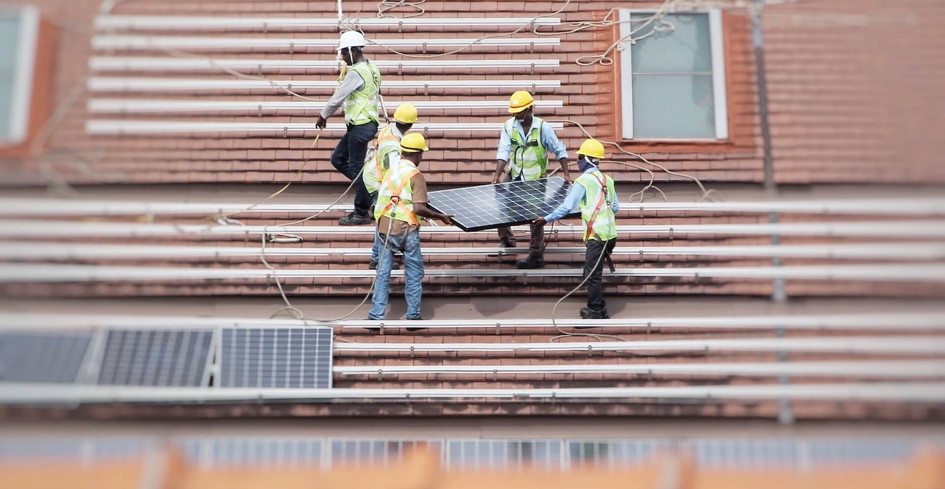Workers installing solar panels on the roof of a business to reduce costs