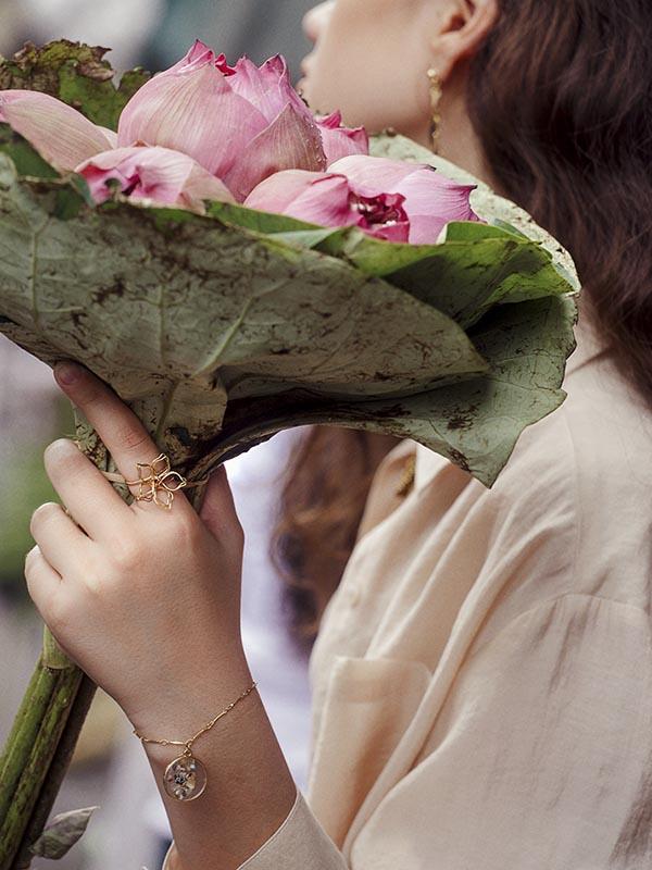 heartland wanderer girl wearing handmade ring and bracelet holding lotus flower