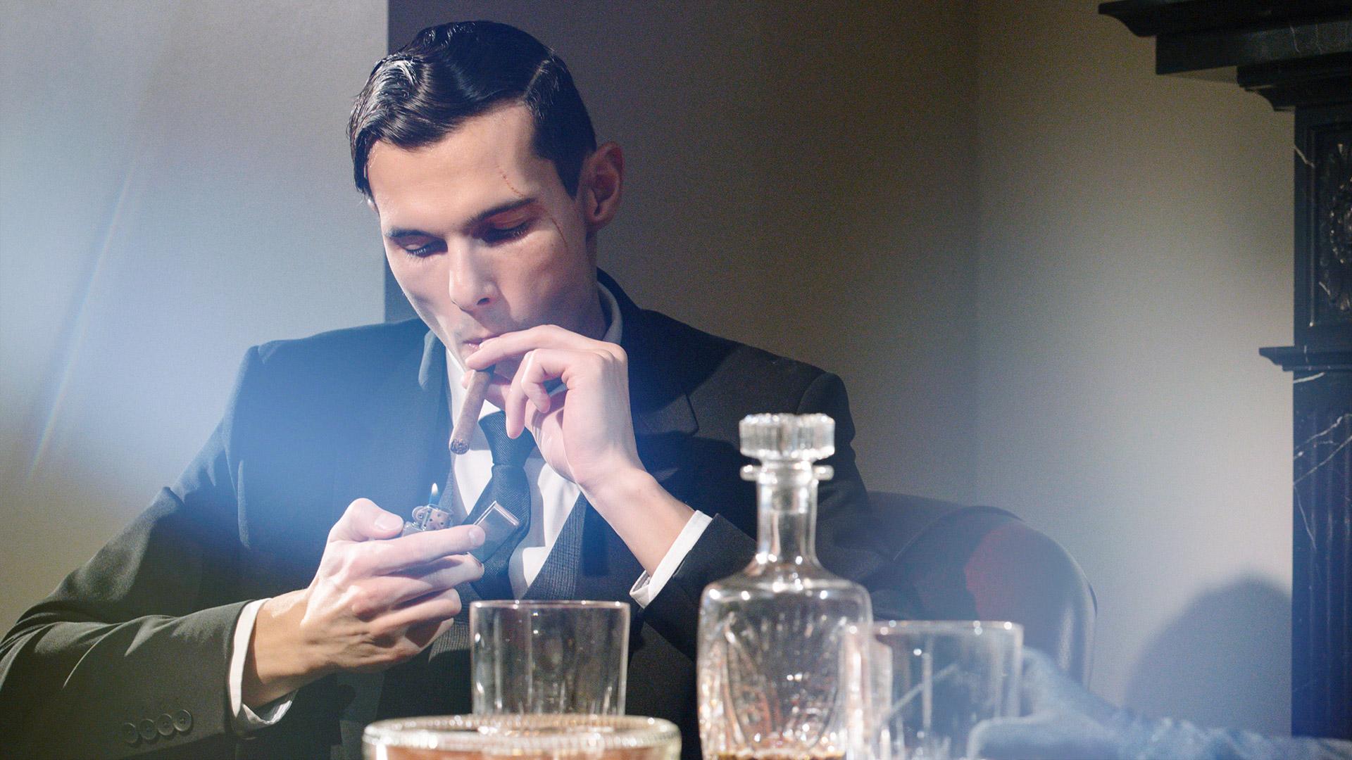 Man zündet sich an einer Bar eine Zigarre an