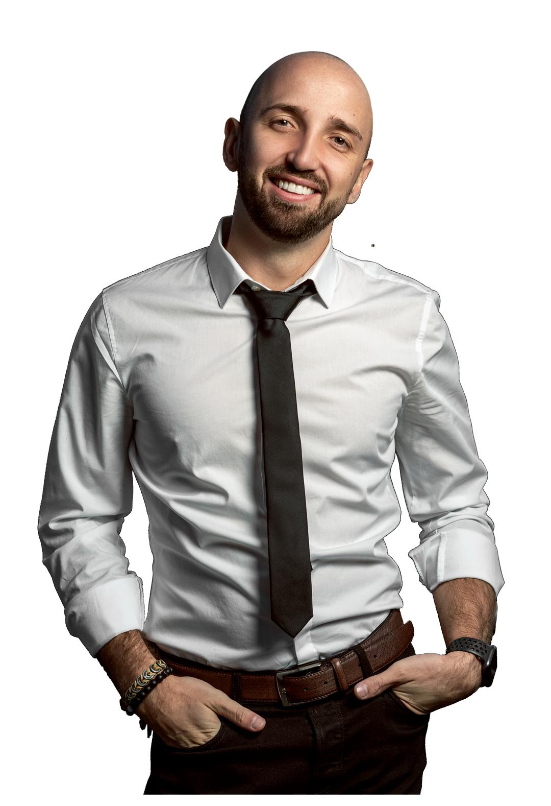 Viktor Stark lächelnd in die Kamera mit weißem Hemd und Krawatte
