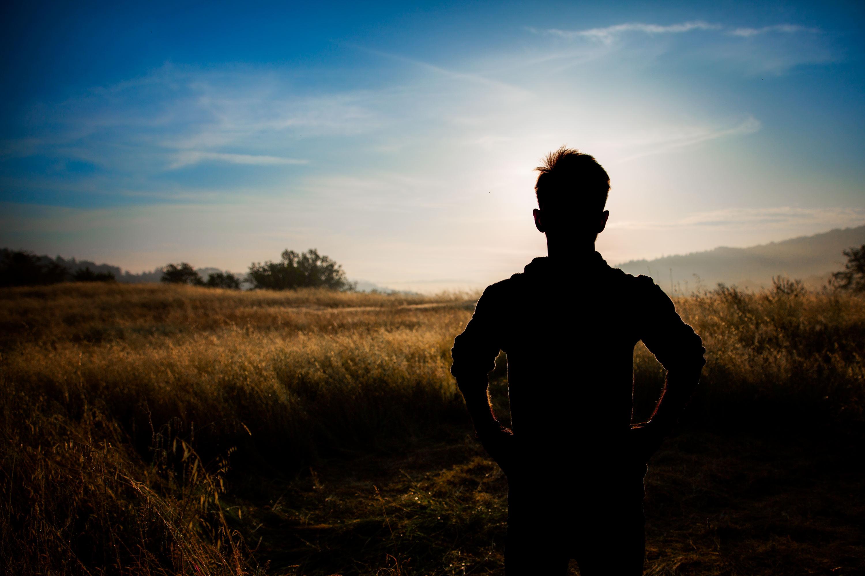 schwarze Person im Feld beim Sonnenaufgang