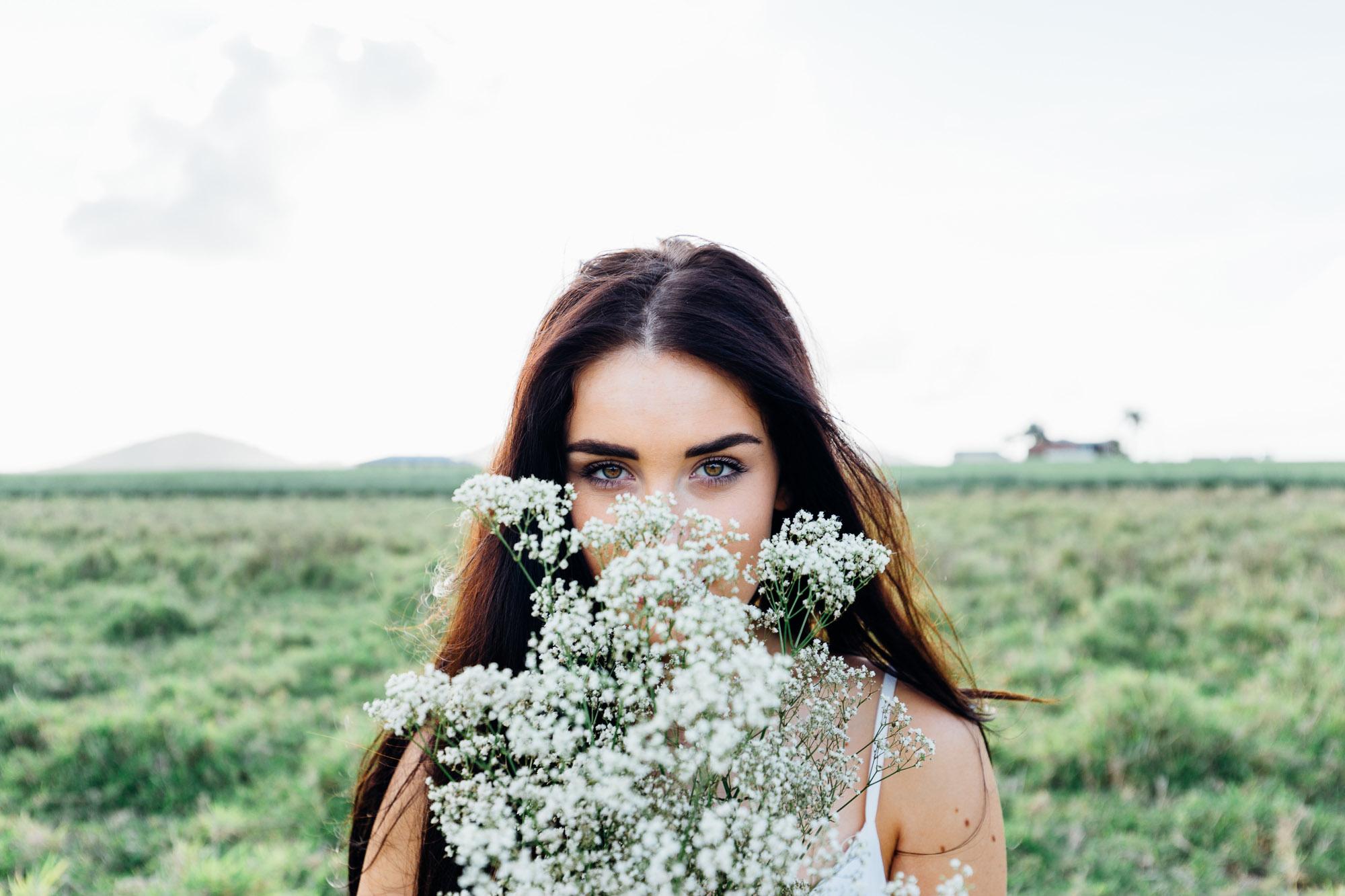Bild einer Braut mit Blumen vor dem Gesicht